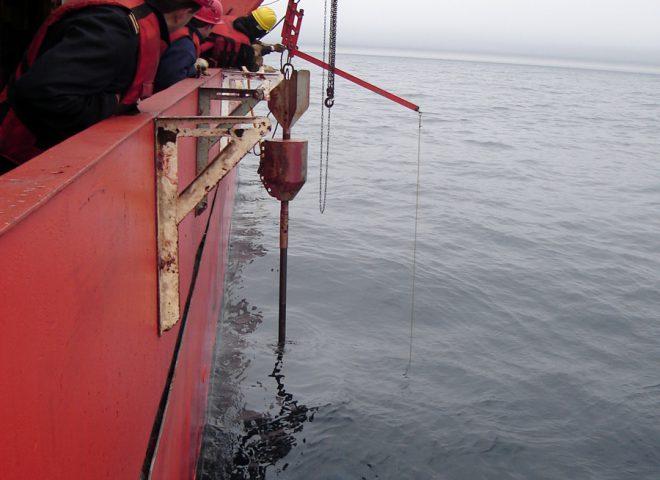 <em>Coring</em> en posición de disparo, para obtención de testigo de sedimentos estratificados del subsuelo. B.O. Pto. Deseado. (Alejandro Tassone – Roberto Violante)